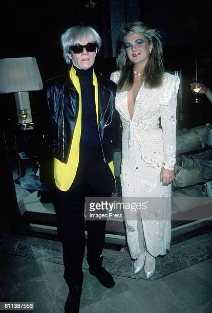 Andy Warhol and Cornelia Guest attend a perfume launch at Macy's circa 1985 in New York City