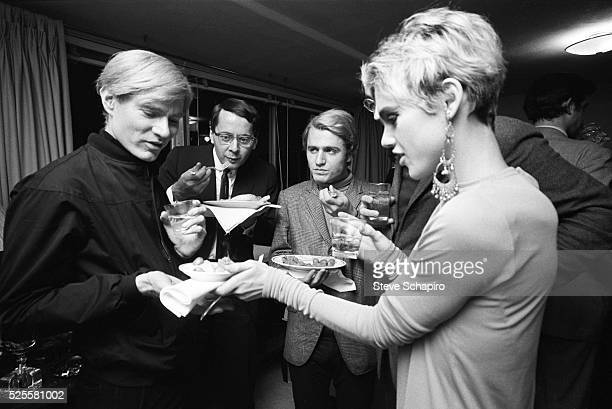 Andy Warhol and Edie Sedgwick eating hors d'oeuvres at party