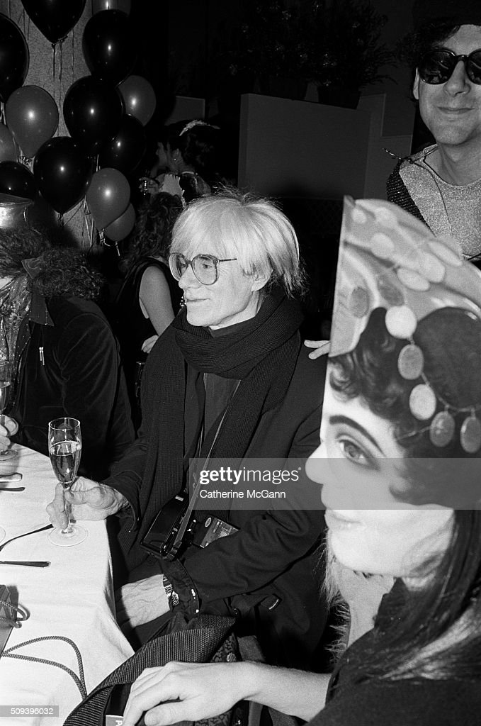 Andy Warhol holds a glass of champagne and smiles as he celebrates his last New Year's Eve with a dinner at Cafe Roma restaurant in New York City, New York. Village Voice writer Michael Musto on right with sunglasses. Warhol died less than two months later on February 22, 1987 (Photo by Catherine McGann/Getty Images).