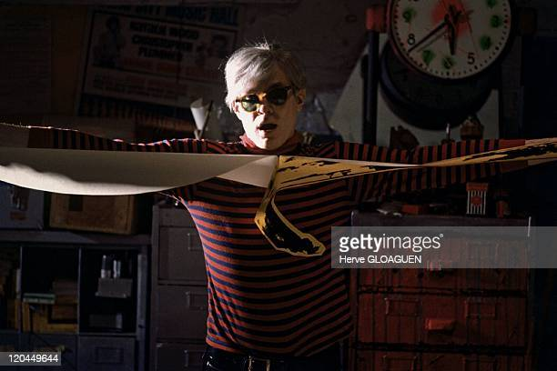 Andy Warhol in New York United States in 1966 Andy Warhol at the Factory get ready to do a collage from a sticker