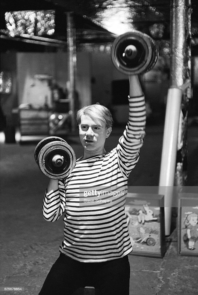 Andy Warhol lifting weights at his studio known as the Factory