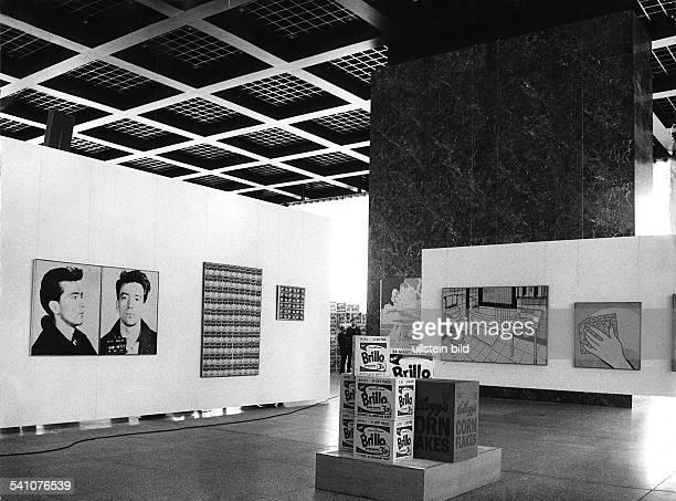 Andy Warhol*Popkünstler Filmproduzent USABlick in einen Ausstellungsraum mit Werken von Warhol und Roy Lichtensteinvorne Brillo Boxes und Kellog's...