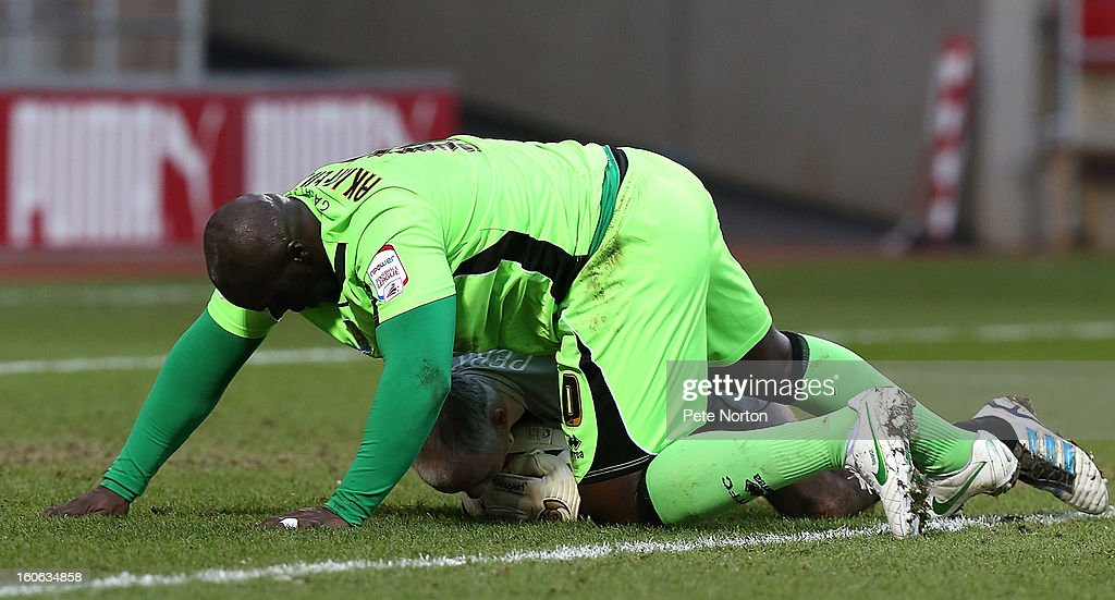 Andy Warrington of Rotherham United collects the ball under pressure from <a gi-track='captionPersonalityLinkClicked' href=/galleries/search?phrase=Adebayo+Akinfenwa&family=editorial&specificpeople=609204 ng-click='$event.stopPropagation()'>Adebayo Akinfenwa</a> of Northampton Town during the npower League Two match between Rotherham United and Northampton Town at New York Stadium on February 2, 2013 in Rotherham, England.