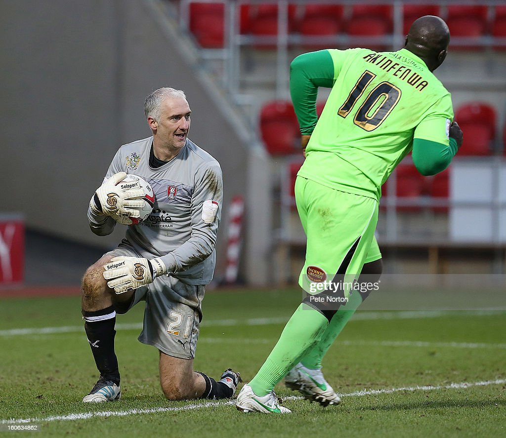 Andy Warrington of Rotherham United collects the ball watched by <a gi-track='captionPersonalityLinkClicked' href=/galleries/search?phrase=Adebayo+Akinfenwa&family=editorial&specificpeople=609204 ng-click='$event.stopPropagation()'>Adebayo Akinfenwa</a> of Northampton Town during the npower League Two match between Rotherham United and Northampton Town at New York Stadium on February 2, 2013 in Rotherham, England.