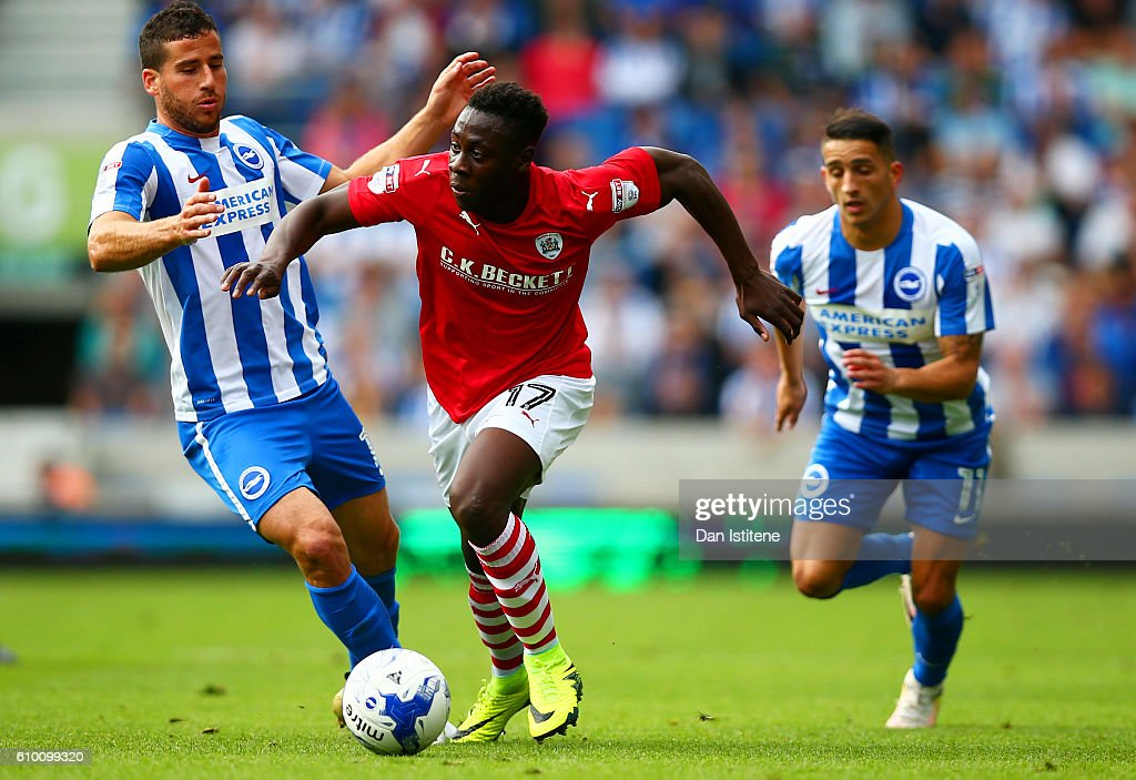 Andy Yiadom of Barnsley battles for the ball with Tomer Hemed and Anthony Knockaert of Brighton & Hove Albion during the Sky Bet Championship match between Brighton & Hove Albion and Barnsley at Amex Stadium on September 24, 2016 in Brighton, England.