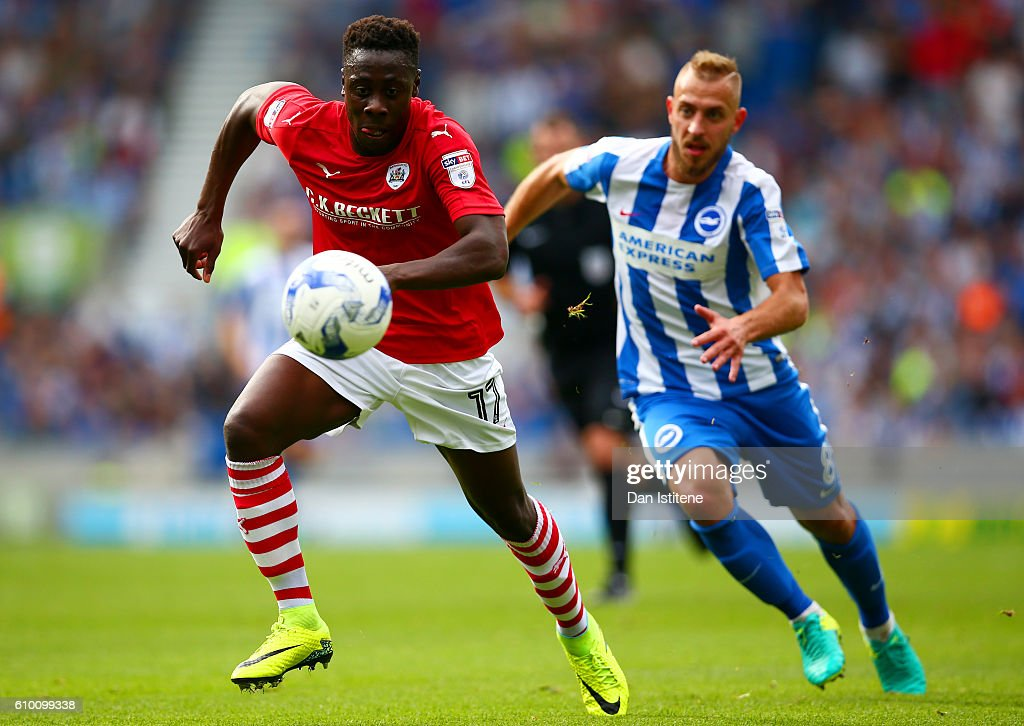 Andy Yiadom of Barnsley runs with the ball under pressure from Jiri Skalak of Brighton & Hove Albion during the Sky Bet Championship match between Brighton & Hove Albion and Barnsley at Amex Stadium on September 24, 2016 in Brighton, England.