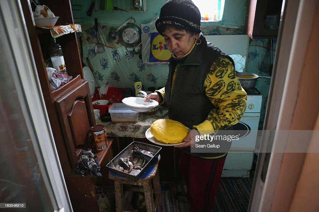Aneta Enache, an ethnic Roma, prepares fried fish and mamaliga, a traditional Romanian dish made from cornmeal, at her home on March 11, 2013 in Dilga, Romania. Aneta's three children all live and work in Italy, send money home and only come to Dilga once a year to visit, while Aneta's grandaughter Madelina lives with her and her husband, who is unemployed after he lost his job at Romania's state-run railways. Dilga is a settlement of 2,500 people with dirt roads and no running water, and unemployment is at 70%. Most of the working-age men and women have at some point worked abroad, mostly in Italy or Great Britain, as many say they are unable to find adequate work in Romania. Romania's Roma belong to a myriad of different tribes defined by their craft, and Dilga's belong to a group called the Rudari, who until the 1930s specialised in woodcrafts. During the communist years most worked in nearby state-run factories and agricultural cooperatives, though the majority of these went bankrupt after 1989 and the local Roma lost their jobs. Since then they have struggled to make ends meet and find a better future for their children, though projects initiated by the European Union and NGOs are helping some to launch small-scale enterprises and improve their children's education.
