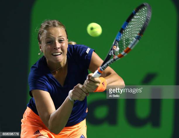 Anett Kontaveit of Estonia returns a shot against Simona Halep of Romania during Day 7 of the Miami Open at Crandon Park Tennis Center on March 26...