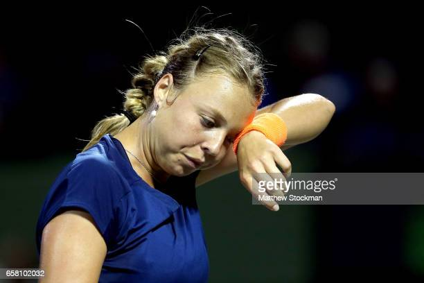 Anett Kontaveit of Estonia wipes her forehead between points while playing Simona Halep of Romania during the Miami Open at the Crandon Park Tennis...