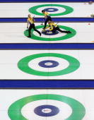 Anette Norberg of Sweden releases the stone as teammates Anna LeMoine and Cathrine Lindahl brush the ice during during the Women's Curling Round...