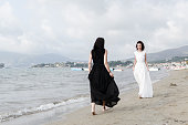 Angel and devil. Two woman walking in new collection dresses white and black on he sandy beach barefooted.