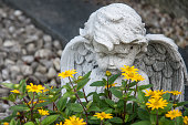 angel and yellow flowers on a grave