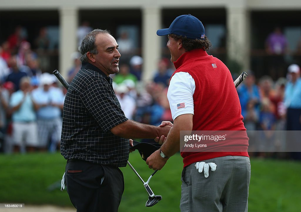 Angel Cabrera of Argentina and the International Team and Phil Mickelson of the U.S. Team shake hands following their match on the 18th hole during the Day Four Singles Matches at the Muirfield Village Golf Club on October 6, 2013 in Dublin, Ohio.