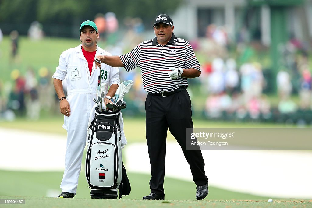 Angel Cabrera of Argentina pulls a club from his bag alongside caddie Angel Cabrera, Jr. during the second round of the 2013 Masters Tournament at Augusta National Golf Club on April 12, 2013 in Augusta, Georgia.