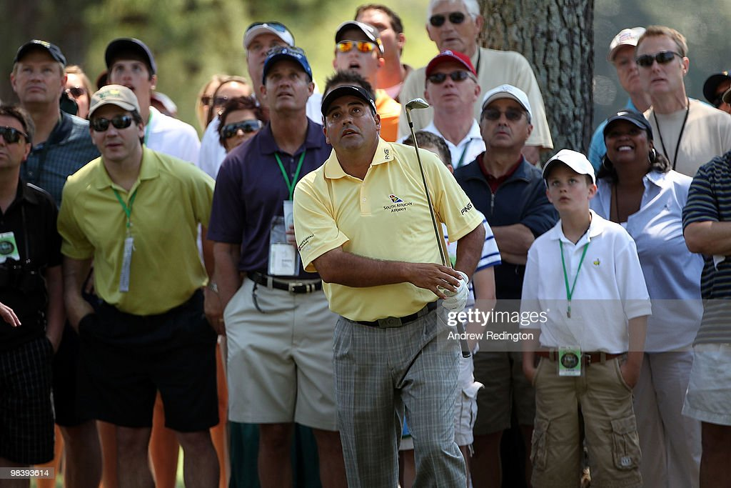 Angel Cabrera of Argentina watches his shot on the first hole in front of a gallery of fans during the final round of the 2010 Masters Tournament at...