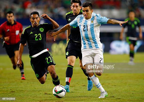 Angel Correa of Argentina runs with the ball up the field as Jose Juan Vazquez of Mexico chases him during a friendly match between Argentina and...