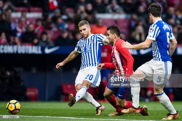 Angel Correa of Atletico de Madrid fights for the ball with Kevin Rodrigues of Real Sociedad and Igor Zubeldia of Real Sociedad during the La Liga...