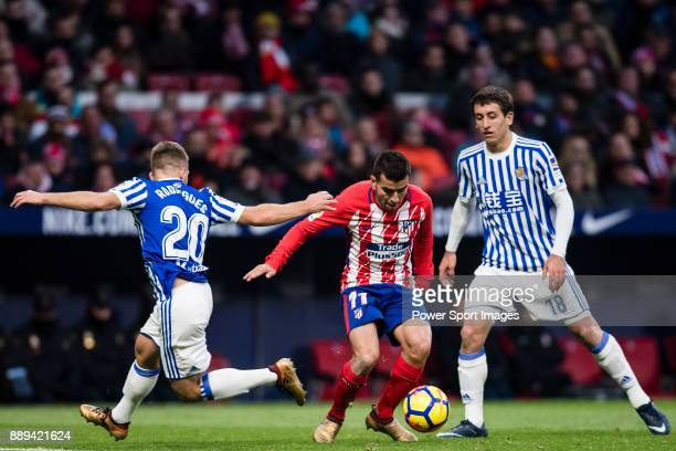 Angel Correa of Atletico de Madrid fights for the ball with Kevin Rodrigues of Real Sociedad and Mikel Oyarzabal of Real Sociedad during the La Liga...