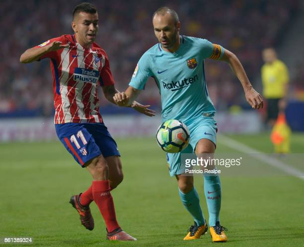 Angel Correa of Atletico de Madrid fights the ball with Andres Iniesta of Barcelona during a match between Atletico Madrid and Barcelona as part of...