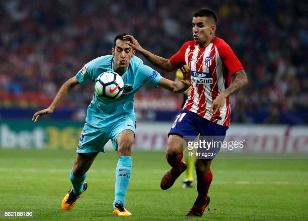 Angel Correa of Atletico Madrid and Sergio Busquets battle for the ball during the La Liga match between Club Atletico Madrid and FC Barcelona at...