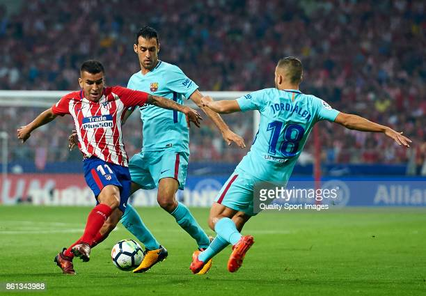 Angel Correa of Atletico Madrid competes for the ball with Sergio Busquets and Jordi Alba of Barcelona during the La Liga match between Atletico...