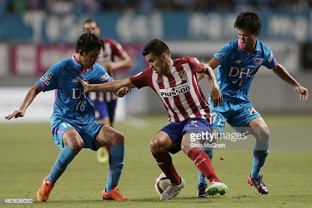 Angel Correa of Atletico Madrid loses the ball under pressure from Choi Sung Keun and Ryosuke Tamura of Sagan Tosu FC during the friendly match...