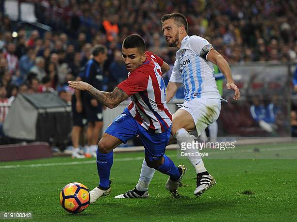 Angel Correa of Club Atletico de Madrid gets past Ignacio Camacho of Malaga CF during the La Liga match between Club Atletico de Madrid and Malaga CF...