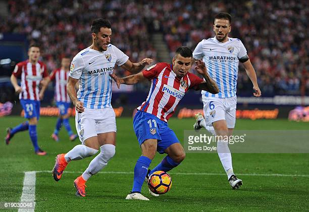 Angel Correa of Club Atletico de Madrid is challenged by Juan Carlos Perez Lopez ''Juancar'' and Ignacio Camacho of Malaga CF during the La Liga...