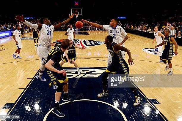 Angel Delgado and Brandon Mobley of the Seton Hall Pirates go for a loose ball against Luke Fischer and Steve Taylor Jr #25 of the Marquette Golden...
