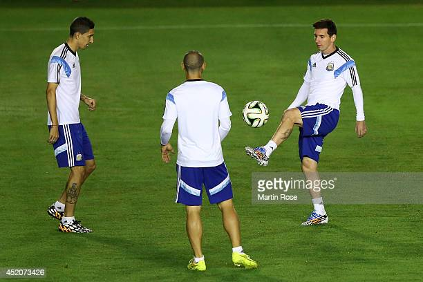 Angel di Maria Javier Mascherano and Lionel Messi of Argentina warm up during the Argentina training session ahead of the 2014 FIFA World Cup Final...