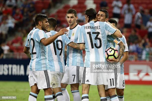 Angel Di Maria of Argentina celebrates with teammates after scoring a goal during the International Test match between Argentina and Singapore at...
