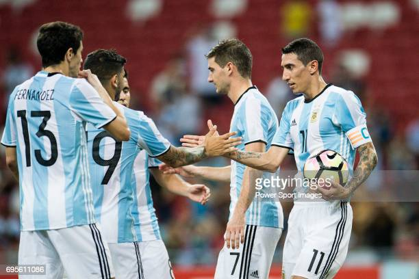 Angel Di Maria of Argentina celebrates with teammates after scoring his goal during the International Test match between Argentina and Singapore at...