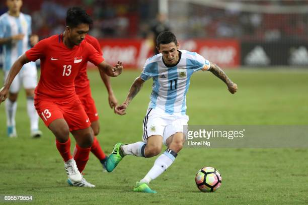 Angel Di Maria of Argentina keeps the ball away from Izzdin Shafiq of Singapore during the international friendly match between Argentina and...