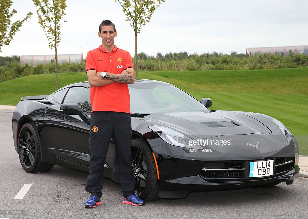 Angel di Maria of Manchester United poses with a Chevrolet car after signing for the club at Aon Training Complex on August 26, 2014 in Manchester, England.