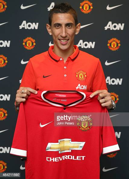 Angel di Maria of Manchester United poses with a Manchester United shirt after signing for the club at Aon Training Complex on August 26 2014 in...
