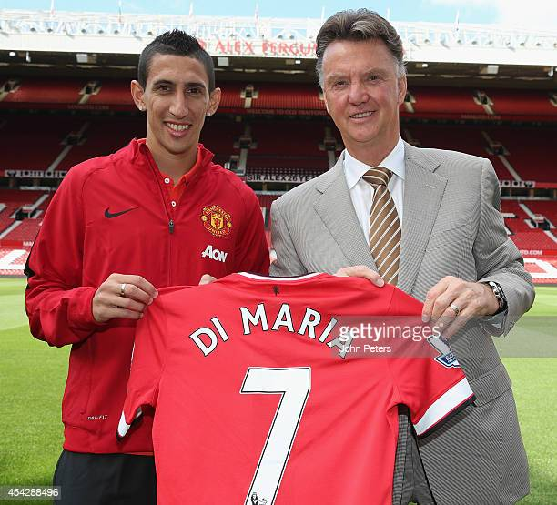 Angel di Maria of Manchester United poses with manager Louis van Gaal and his new shirt number ahead of a press conference to unveil him at Old...