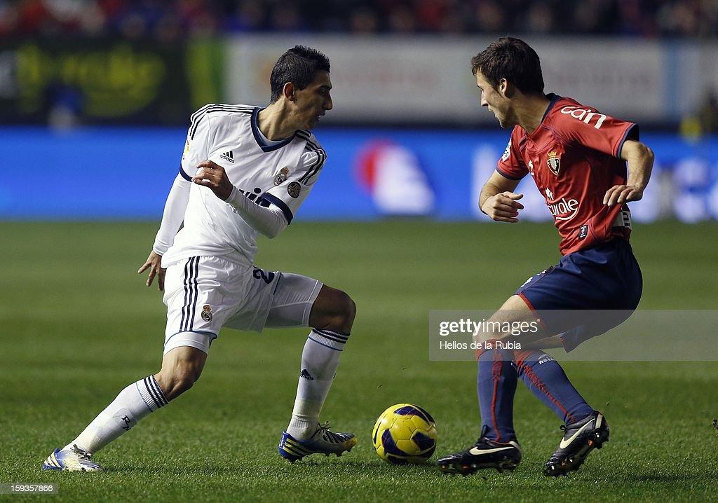 Angel Di Maria of Real Madrid CF battles for the ball with Oier Sanjurjo of CA Osasuna during the La Liga match between CA Osasuna and Real Madrid CF at Estadio Reyno de Navarra on January 12, 2013 in Pamplona, Spain.