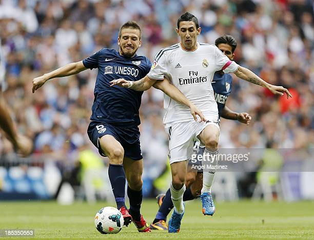 Angel di Maria of Real Madrid competes for the ball with Ignacio Camacho of Malaga during the La Liga match between Real Madrid and Malaga CF at...