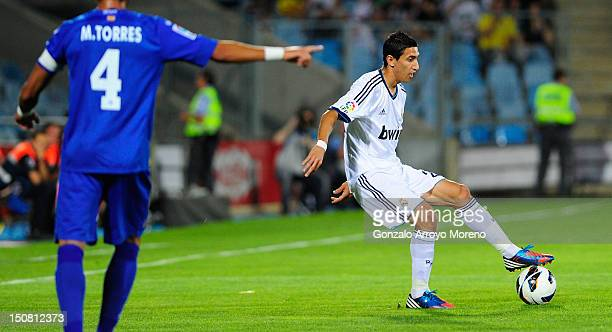 Angel Di Maria of Real Madrid controls for the ball besides him Miguel Torres og Getafe points the pitch during the la Liga match between Getafe and...