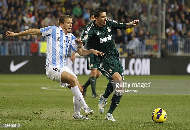 Angel di Maria of Real Madrid is challenged by Ignacio Camacho of Malaga during the La Liga match between Malaga CF and Real Madrid at La Rosaleda...