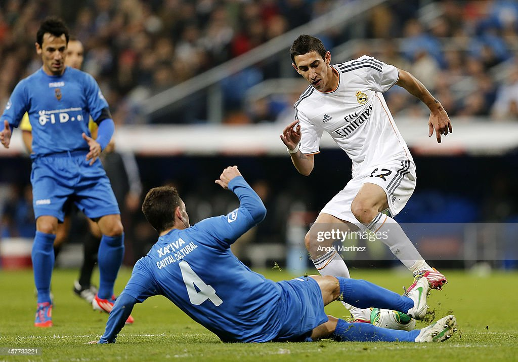 Angel di Maria of Real Madrid is challenged by Pepin of Olimpic de Xativa during the Copa del Rey, round of 32 match between Real Madrid and Olimpic de Xativa at Estadio Santiago Bernabeu on December 18, 2013 in Madrid, Spain.