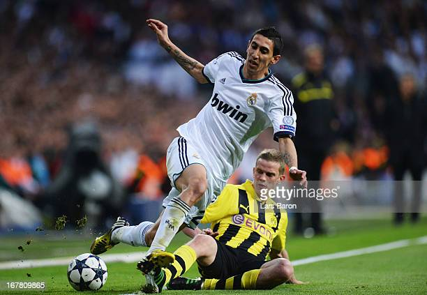 Angel Di Maria of Real Madrid is tackled by Sven Bender of Borussia Dortmund during the UEFA Champions League Semi Final Second Leg match between...