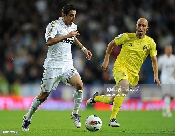 Angel Di Maria of Real Madrid runs for the ball with Borja Valero of Villarreal during the la Liga match between Real Madrid and Villarreal at the...