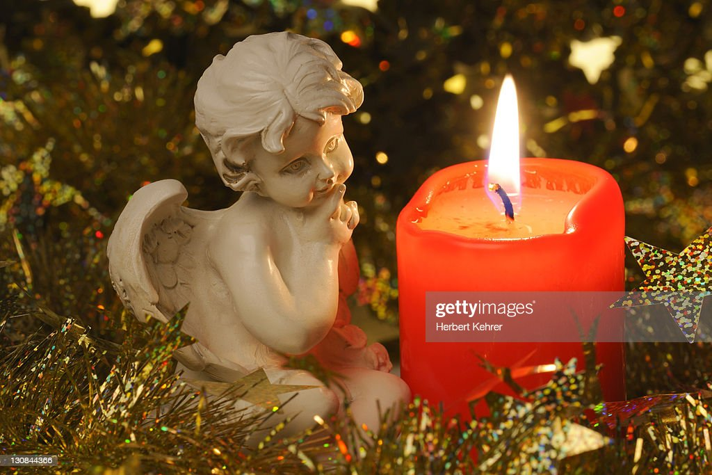 angel figurine beside a burning candle christmas decoration stock photo - Candle Christmas Lights