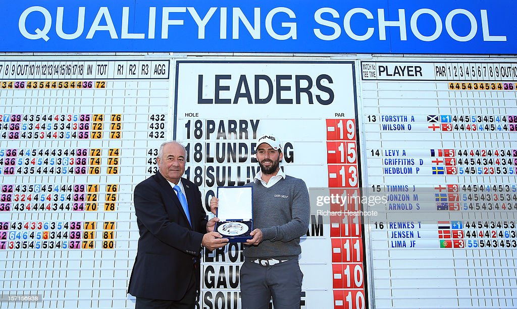 Angel Gallardo, Vice-Chairman of the PGA European Tour Board of Directors, (L) presents John Parry of England with the trophy after the final round of the European Tour Qualifying School Finals at PGA Catalunya Resort on November 29, 2012 in Girona, Spain.