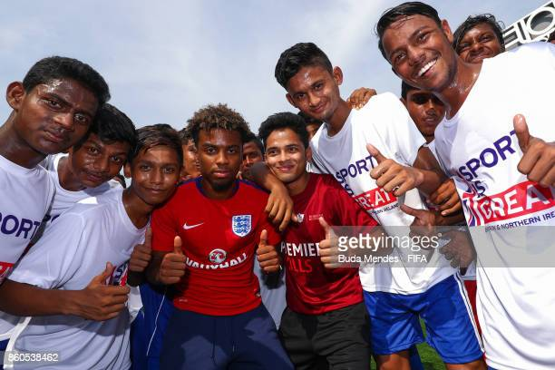 Angel Gomes of England pose for photographers with young children from the Kolkata Outreach programme for a community activity ahead of the FIFA U17...