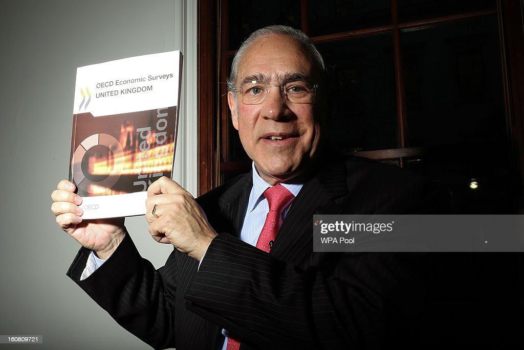 Angel Gurria, Secretary General of the Organisation for Economic Cooperation and Development (OECD), poses with a copy of the OECD surbey at a press conference at The Treasury in Whitehall on February 6, 2013 in London, England. The Secretary-General of the economic think tank attended the press conference to present the OECD's latest Economic Survey of the United Kingdom.