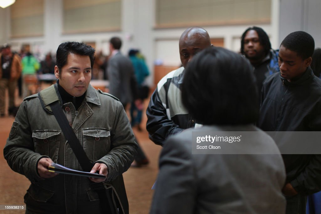 Angel Guzman gets information about employment opportunities with the city during a job fair hosted by the city of Chicago on November 9, 2012 in Chicago, Illinois. Thousands of people started to line up at 3AM for the job fair which did not begin until 9AM. When the doors opened the line was about a half-mile long.