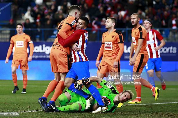 Angel Martin Correa of Atletico de Madrid clashes with Christian Rivera and goalkeeper Yoel Rodriguez of SD Eibar after scoring their second goal...