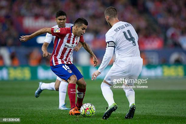 Angel Martin Correa of Atletico de Madrid competes for the ball with Sergio Ramos of Real Madrid CF during the La Liga match between Club Atletico de...